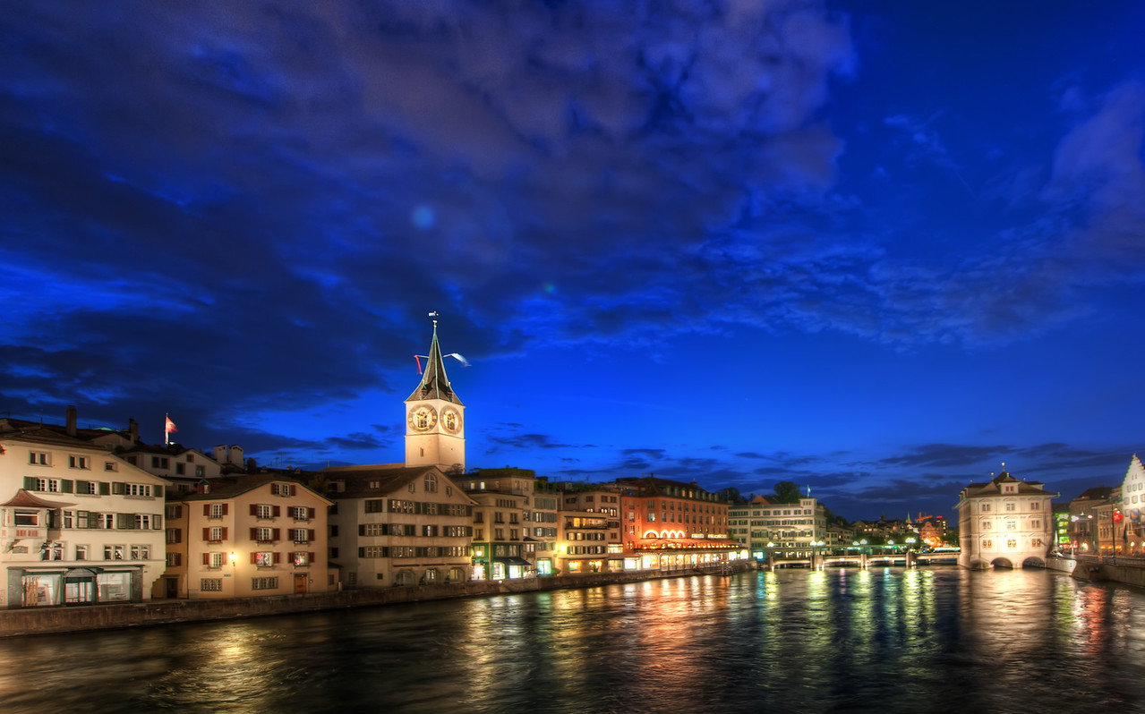 """Soft Zurich at Night These slow-moving huge rivers make for some very nice reflections. With HDR there is a problem of """"ghosting"""" which is when the various frames show different things.  I usually leave the water alone when it gets ghosted because it has sort of an impressionistic feel to it, I think.  In a sense, it gives the """"impression"""" of water, which is somewhere between a photo and our memory.  - Trey Ratcliff More here at the Stuck in Customs blog."""