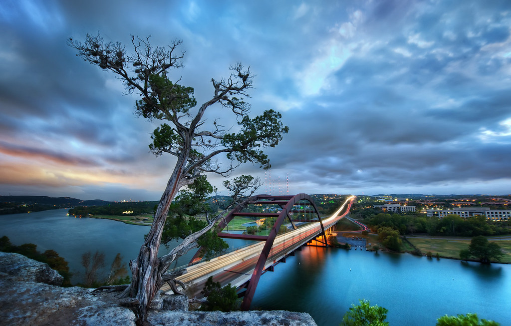 The Pennybacker Bridge This place is right by my house…. I really have no excuse for not going up here almost every night! It takes less than 10 minutes to drive and hike up here… sometimes I actually feel bad about my laziness in this area.It's usually not too crowded up here. Maybe a couple or two will sit and watch the sunset. It's a bit dangerous – a sharp cliff that drops off into the freeway on one side and the water on the other.- Trey RatcliffClick here to read the rest of this post at the Stuck in Customs blog.