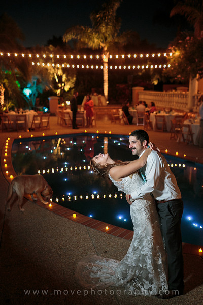 A bride and groom posing for a wedding photo by a swimming pool at a private estate wedding in Santa Barbara.