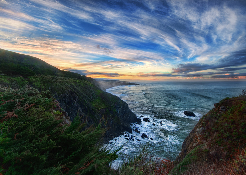 """<h2>Big Sur in the Morning</h2> <br/>5:30 AM.  Alarm goes off.  It's always painful.  People that say they are """"morning people"""" -- I think they are lying.  But, when in a beautiful place, I always force myself, military style, to pop out of bed.  There are hikes to be made and photos to take!<br/><br/>I stayed at the Ragged Point Inn.  My room had a little fireplace and everything (which made it even harder to get out of bed!).  After I got downstairs, I started a little hike to get a good vantage of the coast and the sunrise.  Of course, there was a fence blocking the best bit, so I jumped over it like Carl Lewis (a much older, whiter, and less jumpy Carl Lewis), and edged along the rocky coast to get a good spot.  I forgot to put on my hiking shoes and mistakenly donned my Cole-Haans while in the dark.  Big mistake.  Those don't make for good hiking shoes, especially after five minutes of getting soaked in morning dew from the foliage I was ripping my way through.<br/><br/>But, I had on my earphones and was blasting away music...  all was good... the sun came up, the clouds were perfect, and I took this photo.<br/><br/>- Trey Ratcliff<br/><br/><a href=""""http://www.stuckincustoms.com/2010/01/31/driving-up-the-pacific-coast-highway/"""" rel=""""nofollow"""">Click here to read the rest of this post at the Stuck in Customs blog.</a>"""