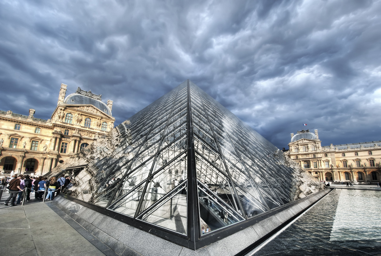 The Louvre in Heavy Clouds People are always around this thing!  If you've been there, then you know what I mean... getting a clean shot is almost impossible, unless you visit just after sunrise.  In this case, I don't photoshop out the people, but I minimize them... so the photo isn't really about the people, it's about the Louvre.  But, with a wide angle lens, you have to get right up on the thing.  - Trey Ratcliff  From the blog post here at stuckincustoms.com