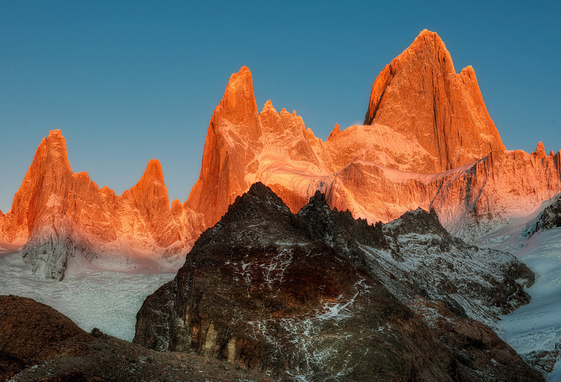 "<h2>A Razor to the Sky</h2> <br/>As is the case with every day here, I have also included a photo.  This is of the indomitable Fitz Roy at sunrise buried deep in the Andes, in the hinterland between Argentina and Chile.  To get this shot, it was none too easy!  First, I ""woke"" up after a sleepless night in a two-man tent with Yuri.  It was perhaps the worst night of my life and I've never had a panic attack before, but I honestly felt like I was pretty close.  The smell combined with the pitch black, the snoring, the freezing cold, and the tiny tent was almost more than I could bear!<br/><br/>I woke up around 4:30 AM with -7 Celsius temperatures.  It was bitter cold.  I got dressed QUICKLY in the pitch black cold and then headed off with two of my Russian friends to begin scaling the mountain.  They had lights on their hats;  I did not.  I walked between them, trying not to slip on the icy ""trail"" between the dodging shadows cast by their headlights.  I'll never forget it for the rest of my life.  We ascended 1,500 feet in less than 45 minutes so we could catch the pink rays of sunrise just as they hit the peaks.<br/><br/>Last, I have been interviewed about photography and more on the <a href=""http://www.prophotoshow.net/blog/2009/04/14/pro-photography-podcast-57-photography-hdr-with-trey-ratcliff/"" rel=""nofollow"">Pro Photo Show</a>.  It's a free podcast that you can listen to if you want to know more about the process or just hear me ramble on about stuff you may or may not find interesting!<br/><br/>- Trey Ratcliff<br/><br/><a href=""http://www.stuckincustoms.com/2009/04/18/patagonia-in-autumn-a-short-film/"" rel=""nofollow"">Click here to read the rest of this post at the Stuck in Customs blog.</a>"