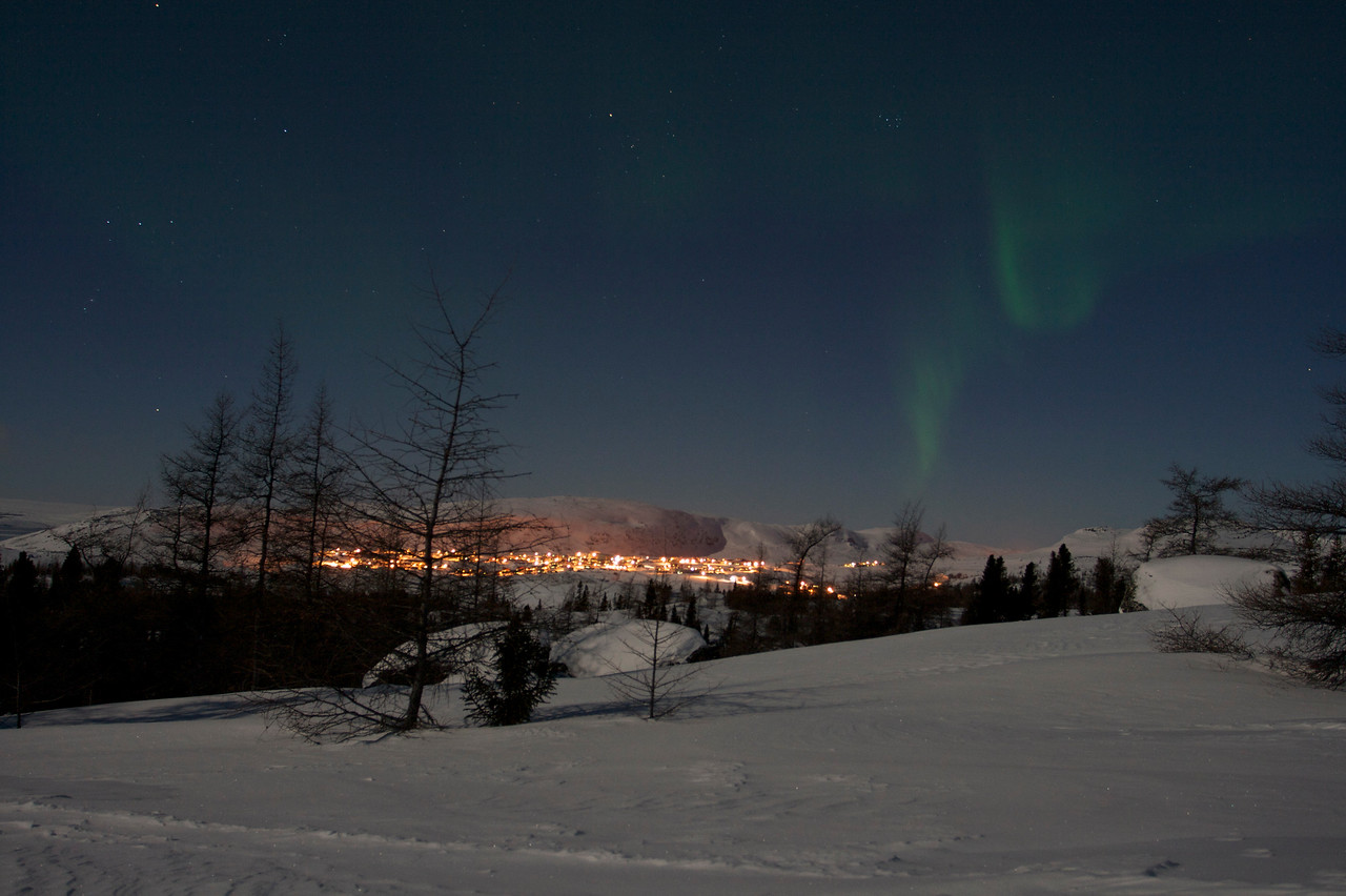 The Northern Lights or Aurora Borealis as seen from Northern Quebec, Canada. The lights you see are from the small town of Kangiqsualujjuaq, which is located above the tree line.<br /> At the time of taking this photo the temperature was -37 degrees Celsius.