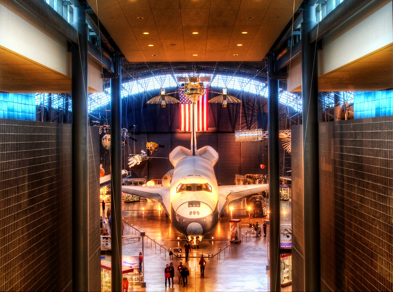 """The Shuttle in Spacedock I finally got to see the Space Shuttle!  It's one of those things a young boy always dreams of seeing, don't you know?  I'm still waiting on that phone call from NASA where they invite me to see one blast off.  I'd love to do a creative shot there…This was shot in the new Air and Space Museum on DC.  Yes, not that old one that I used to think was cool when I was a kid.  This is a new and improved center that is completely unbelievable. I had a small argument with a security guard that would not let me take my tripod.  He said I needed a """"blue card"""".  I asked how to get that and he said the only person that could possibly give it to me was probably at home.  There were a number of bureaucracies where I could have filed a series of complaints, but only if such complaints were filled out in a way as pre-approved by other bureaucracies.  I did send out a self-serving Tweet to @Smithsonian asking them for special dispensation — I hoped to sway them since, after all, one of my photos did hang in the Smithsonian.  They did indeed respond, but one day late. So, I'll still keep @Smithsonian on one of my Five Twitter Lists.So, I was forced to take my HDR shots with a hand-held pose.  How barbaric and depressing.  I would try to wedge myself up against a beam or a foreigner when possible, but that rarely works out as good as a tripod.  Those things are never placed in the right compositional spots, sadly.But, I did have the Nikon D3S as a backup, and I fired this one off.  It was a 4-exposure HDR from -2 to +1.  ISO 400, 23mm, f/6.7 and 1/6 second shutter speed. The +2 exposure was too blurry, and I got most of the light I needed out of the +1 anyway.- Trey RatcliffClick here to read the rest of this post at the Stuck in Customs blog."""