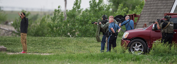 A previously barricaded suspect looks over his shoulder at law enforcement officers before he is taken into custody in a trailer park on Mansfield Road. Officers were called to the scene after a man was shot inside his car and subjects fled into a nearby home.