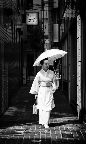 Umbrella in the Sun Tokyo has so many neighborhoods! There are dozens and dozens, each one like it's own mini-city with its own culture and memes. This one (I'm afraid I've forgotten the name) is filled with an older, traditional feel. It's not uncommon to see women come out and walk the street in traditional dress.- Trey RatcliffClick here to read the rest of this post at the Stuck in Customs blog.