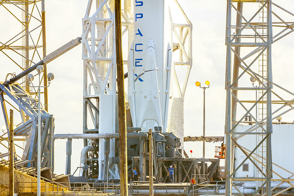 SpaceX Falcon 9 resting vertically at Launch Complex 40 in Cape Canaveral as workers below prepare the rocket for launch.