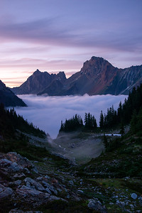 Fog fills the valley beneath Canadian Border Peak and American Border Peak which you guessed it, marks the international boundary of America and Canada as seen from the Mount Baker Wilderness in Washington.