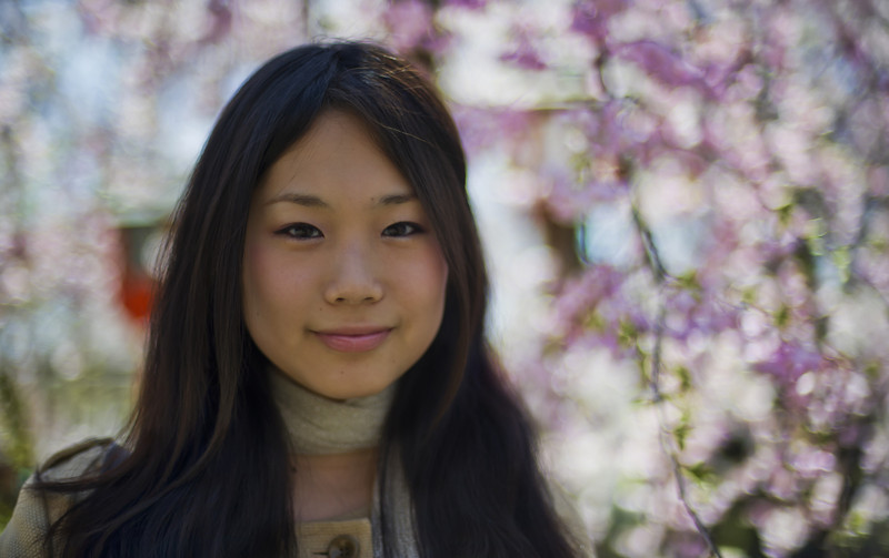 """<h2>Pretty Girl in Cherry Blossoms</h2> <br/>I started riding the wave of the cherry blossom bloom in Osaka before ending up here in Kyoto.  All the news stations in Japan have a long nightly report that shows a fluttering line of pink cherry blossoms that flow across the map from the west to the east.<br/><br/>It's a huge national celebration -- and it's really fun to be part of the sensation.  There are hundreds of tiny and large parks all over the country that have cultivated gardens of these special trees.  I visited a few dozen, and I enjoyed wandering around taking photos while the blossoms fell down like gentle pink snow.  Millions of Japanese people also go out to enjoy the event.  This girl was standing alone under a tree, taking photos and just sort of smiling, enjoying everything.  I gave her the international sign for """"mind if I take a photo???""""  She gave me a little bow along with a mouth-covering giggle before relaxing into a smile.<br/><br/>- Trey Ratcliff<br/><br/><a href=""""http://www.stuckincustoms.com/2010/12/13/pretty-girl-in-cherryblossoms/"""" rel=""""nofollow"""">Click here to read the rest of this post at the Stuck in Customs blog.</a>"""