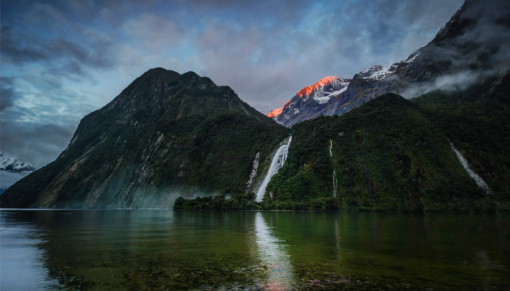 Bowen Falls in Milford Sound This is one of many sights we'll be seeing together if you come down here to New Zealand. This place is quite the turkey shoot! There's beautiful bits all around.The best way to get to this particular spot is to get off the walking path and work your way across the rocks. I prefer the view where you are looking across the water… The conditions change quite violently depending on the light and the amount of rain. Sometimes, after a fresh rain, that waterfall is absolutely insane! In this photo, it's still pretty crazy, but only of average sanity.- Trey RatcliffClick here to read the rest of this post at the Stuck in Customs blog.