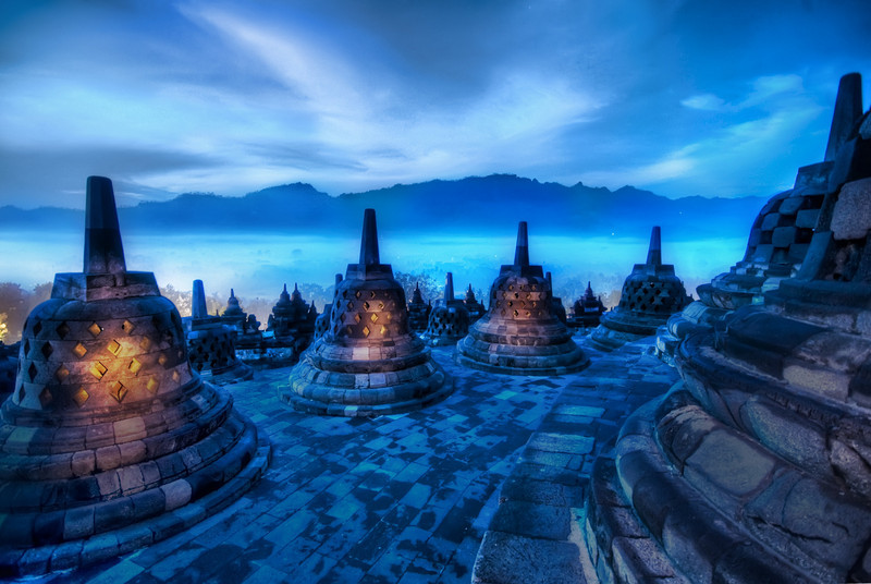 """<h2>The Beating Hearts of the Buddhas</h2> <br/>The morning fog coming off the top of the jungle trees was not like anything I had seen before.  There was just enough morning light to give everything a twilight blue and paint the mountains in the distance a deeper color.<br/><br/>I tried something a little bit different with this photo.  I was holding two flashlights to help me climb the temple in the morning. I think I got there about 5:30 AM when it was still pitch black, so the flashlights helped me find the right footholds and whatnot.  Anyway, this was an extremely long exposure, so I used some of that time to """"paint"""" the inside of the bell cages with the beams of my flashlights.  Each of those bell cages held a solitary outward-facing Buddha.  I'm glad I was there alone, because I'm sure I looked like a loon running around shining the flashlights in patterns to illuminate the Buddhas inside.<br/><br/>- Trey Ratcliff<br/><br/><a href=""""http://www.stuckincustoms.com/2009/06/23/the-beating-hearts-of-the-buddhas/"""" rel=""""nofollow"""">Click here to read the rest of this post at the Stuck in Customs blog.</a>"""