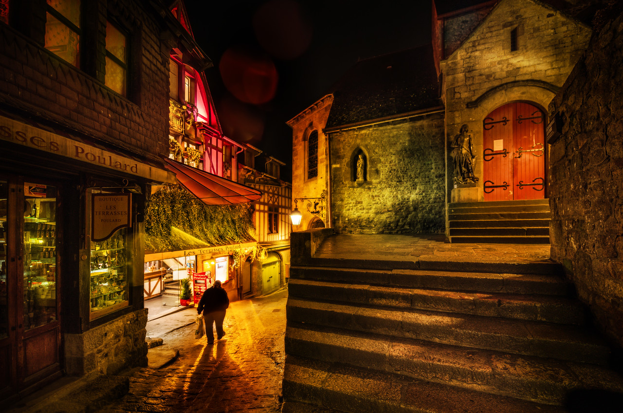 Exploring the Medieval Mont Saint Michel I think if you ever go to Mont Saint Michel that you should really try to stay up on the island. Hotel space is extremely limited, but it gives you the chance to walk around the old walled city deep into the night. All the tourists are gone, and the only people around are the supposed 46 people that live there, according to Wikipedia.Here, an old man walks home after a day at work.- Trey RatcliffClick here to read the rest of this post at the Stuck in Customs blog.