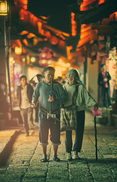 "<h2>Walking Blind through China</h2> As Tom Anderson and I were leaving the old area of Lijiang one evening, we saw these two coming towards us in the opposite direction. One of them was blind (perhaps both), and one played a small stringed instrument while the other held out a bowl for donations.<br><br>I squatted down and waited for them to enter a little pool of light from a nearby shot before I took the photo. And then I walked over and put a little donation in the bowl.<br><br>- Trey Ratcliff<br><br><a href=""http://www.stuckincustoms.com/2012/01/08/walking-blind-through-china/"" rel=""nofollow"">Click here to read the rest of this post at the Stuck in Customs blog.</a>"