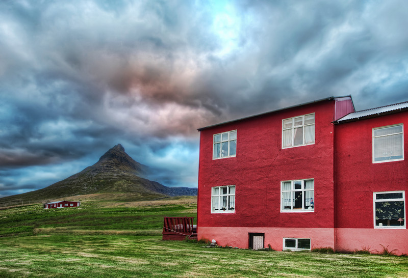 "<h2>Green Mountain, Red House</h2> ""Is the house really THAT red?"" my wife asks me.  Yes, oh yes, it is...  But now I am taking her to Iceland with me, so she can see these bright colors for herself...  I don't know if it's a Scandinavian thing or what, but we just don't see colorful houses like this in the states.  I think we either have brick, or white, or slightly off-white, or perhaps a light beige, or maybe something daring like a mauve-eggshell-white...  I mean, I'm just as bad... mine in stucco.  I don't even think my homeowner's association would let me paint it red.  But, knowing Austin, with a bright red house, we'd probably have a few commies show up in Che Guevara shirts, wondering where the free pizza is...  - Trey Ratcliff  Read more <a href=""http://www.stuckincustoms.com/2011/06/15/green-mountain-red-house/"">here</a> at the Stuck in Customs blog."