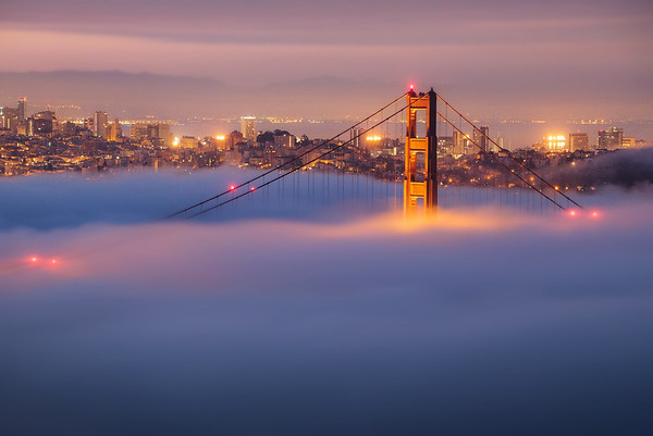 The Golden Gate Bridge peaks through a blanket of fog