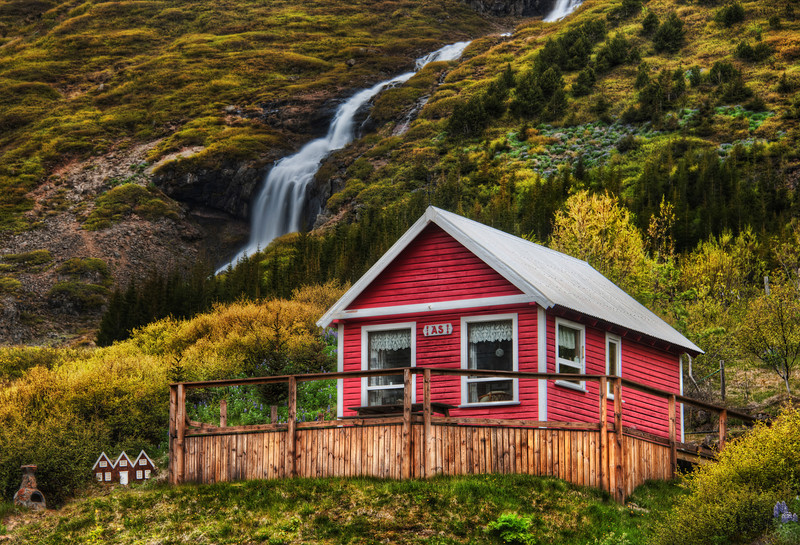 "Little Elves, Little Waterfall Going into one of the valleys by Isafjordur takes you to many little homes near waterfalls.  I thought this one was quite lovely.  And if you look to the left there, you'll see the tiny homes they also built for the elves.  I was editing this photo at dinner one evening in Isafjordur.  One of the waitresses saw this house, recognized it, and said, ""Oh that's jklasdj(jkasdj^dhsaj"".  Of course, I am doing my best to approximate the Icelandic language there...  - Trey Ratcliff  Read the rest here at the Stuck in Customs blog."