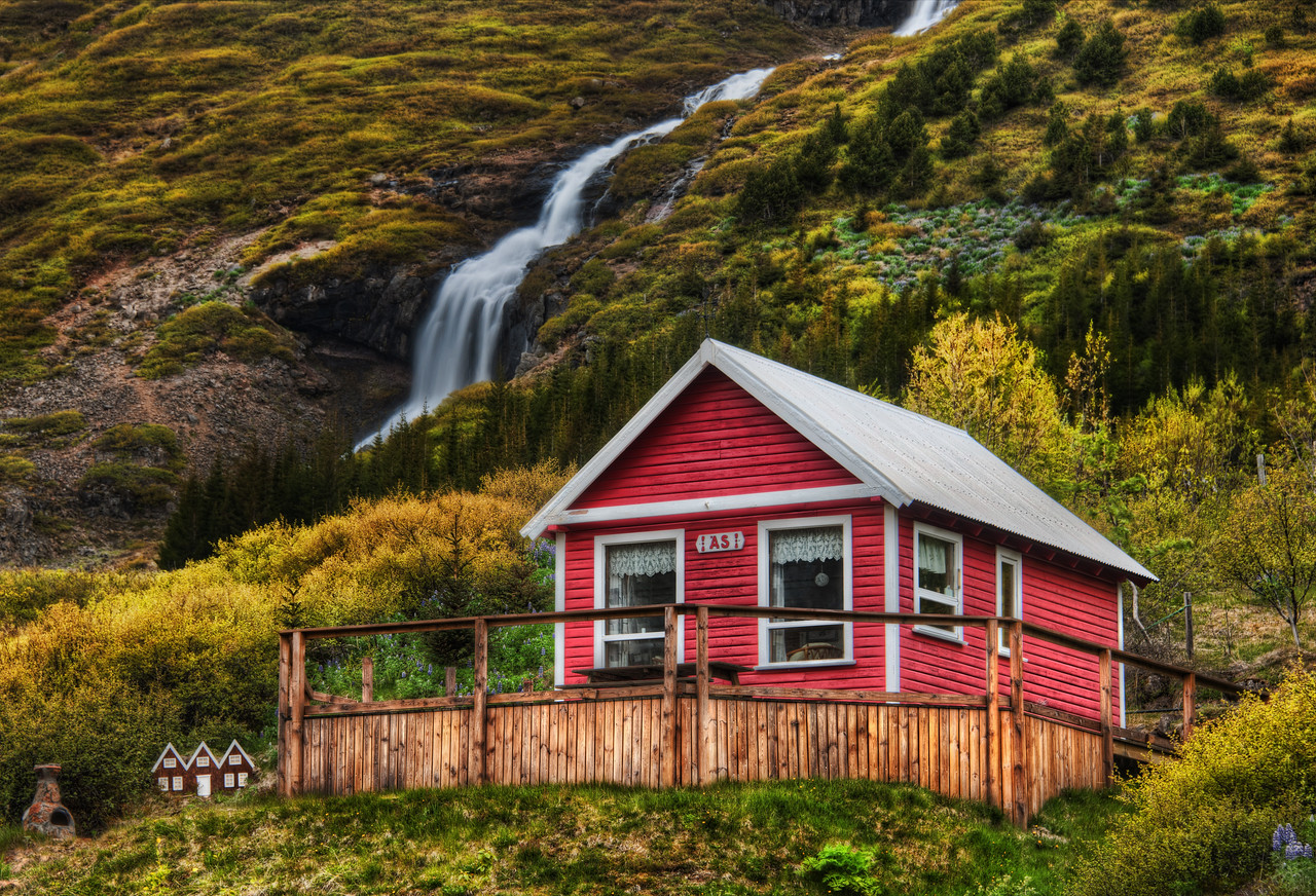 """Little Elves, Little Waterfall Going into one of the valleys by Isafjordur takes you to many little homes near waterfalls.  I thought this one was quite lovely.  And if you look to the left there, you'll see the tiny homes they also built for the elves.  I was editing this photo at dinner one evening in Isafjordur.  One of the waitresses saw this house, recognized it, and said, """"Oh that's jklasdj(jkasdj^dhsaj"""".  Of course, I am doing my best to approximate the Icelandic language there...  - Trey Ratcliff  Read the rest here at the Stuck in Customs blog."""