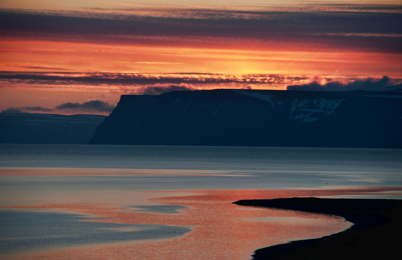 """<h2>Waiting on the Solstice Sun</h2> Up in the northwest fjords of Iceland, the roads end but the land keeps going.<br><br>There is this distant island, pictured here, that has no roads at all. It seems so remote and... well... scary. I don't know why I get that foreboding sense! It just feels so lonely, so far north... the cliffs are so sheer... no one to hear you scream... and these sorts of things. I do like being remote, but this is a little too remote.<br><br>- Trey Ratcliff<br><br><a href=""""http://www.stuckincustoms.com/2012/01/07/waiting-on-the-solstice-sun/"""" rel=""""nofollow"""">Click here to read the rest of this post at the Stuck in Customs blog.</a>"""