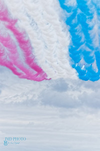Dynamic Red, white and blue colour trail left in the sky by The Red Arrows RAF aerobatic flying display team peforming a fly-past at Great Yarmouth