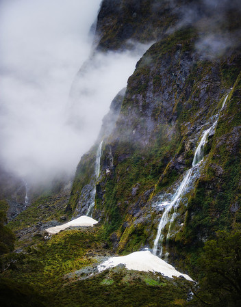 Waterfalls on the way to Milford Sound There is a good question that will never be answered: Is the drive to Milford Sound equal to the epicness of Milford Sound itself? No one knows!! I can't figure it out. But, one random element that comes into the equation is the rain. When it is raining (or a recent rain), there are over 100 waterfalls that decorate the steep valley.It's kind of hard to shoot waterfalls in the rain. Actually, it's really hard. I usually amp up my ISO and drop my F-stop very low to make sure I get a quick picture before the rain settles on my lens.- Trey RatcliffClick here to read the rest of this post at the Stuck in Customs blog.