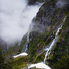 "<h2>Waterfalls on the way to Milford Sound</h2> <br/>There is a good question that will never be answered: Is the drive to Milford Sound equal to the epicness of Milford Sound itself? No one knows!! I can't figure it out. But, one random element that comes into the equation is the rain. When it is raining (or a recent rain), there are over 100 waterfalls that decorate the steep valley.<br/><br/>It's kind of hard to shoot waterfalls in the rain. Actually, it's really hard. I usually amp up my ISO and drop my F-stop very low to make sure I get a quick picture before the rain settles on my lens.<br/><br/>- Trey Ratcliff<br/><br/><a href=""http://www.stuckincustoms.com/2013/04/04/waterfalls-on-the-way-to-milford-sound/"" rel=""nofollow"">Click here to read the rest of this post at the Stuck in Customs blog.</a>"