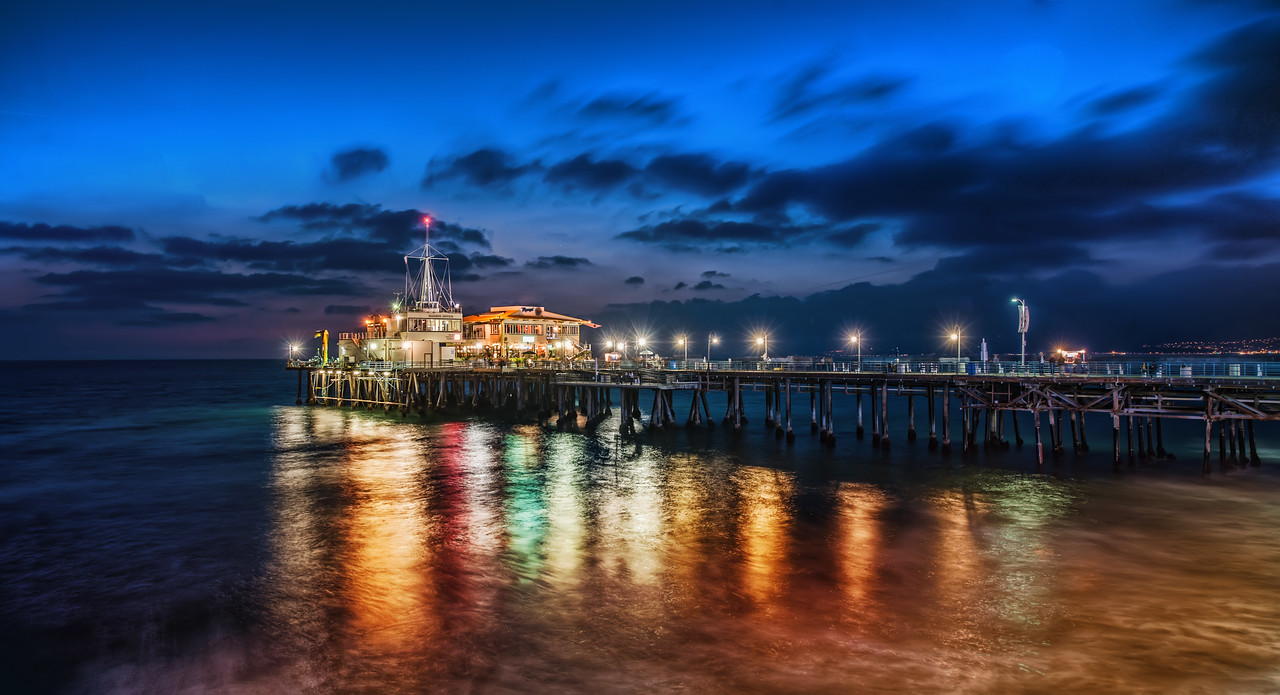 The Pier in Santa MonicaAfter we finished shooting down on the beach, we moved the photowalking party up to the pier.  There was just an edge of light left when I took this photo.The dock is in two parts.  The first part has the amusement park and the second part extends further out into the sea.  Sometimes docks aren't so great for night shots because they are shaky and move with the waves.  But this one was pretty solid — I suppose because of the rides and whatnot that also need to be stable.  Anyway, it was more than steady enough for the very long exposures need for the shot.- Trey RatcliffClick here to read this post at the Stuck in Customs blog.