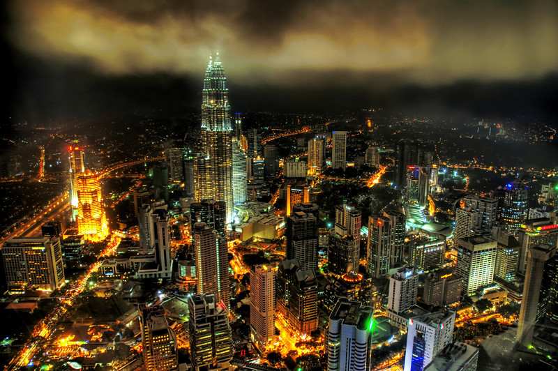 "<h2>Blowtorch</h2> <br/>I understand from my mom that Kuala Lumpur was also one of my grandfather's favorite cities.  He used to work for Exxon, back in the middle of the 20th century.  It's hard for me to imagine what it looked like back then.  It's too bad I wasn't ever able to show him this photo to see his reaction.<br/><br/>KL is called one of the Asian ""small tigers"" because of its booming economy in the last 20 years or so.  Many Asian cities are very pretty with unique architecture.  Since many of them are so ""new"", the architecture is often much more modern than their Western counterparts. In this one, you can see the gargantuan twin Petronas towers looming high over the city, poking up into some clouds.<br/><br/>- Trey Ratcliff<br/><br/><a href=""http://www.stuckincustoms.com/2006/12/03/blowtorch/"" rel=""nofollow"">Click here to read the rest of this post at the Stuck in Customs blog.</a>"