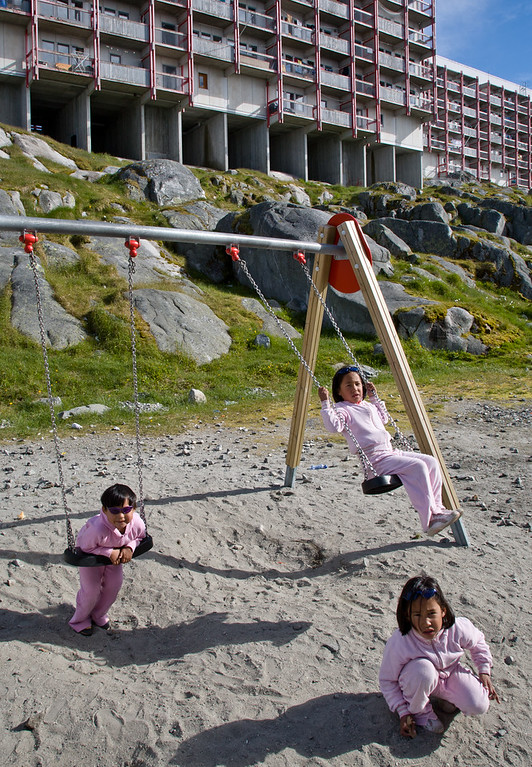 Children play on a swing in front of apartment blocks, Nuuk, Greenland
