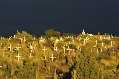 The San Juan Mission Cemetery was founded in 1918.  Just south of Farmington NM, I found it recently near sundown on a stormy afternoon, the light was amazing and the mission chapel was in the background.  The graves are unmarked except for the simple wooden crosses.
