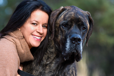 Headshot portrait of a smiling young woman with long dark hair wearing a light brown sweater, hugging her dark brindle colored English Mastiff dog.