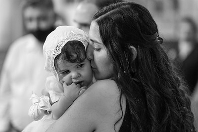 A mother kisses her baby and holds her close shortly after a baptism ceremony. 07-26-2020
