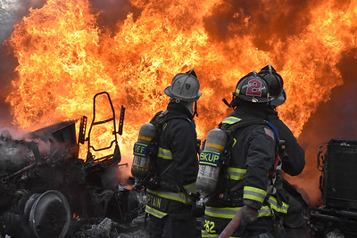 East Farmingdale firefighters work to man-handle a 2 1/2 inch hose in order to extinguish a large multiple truck fire. 03-03-2018