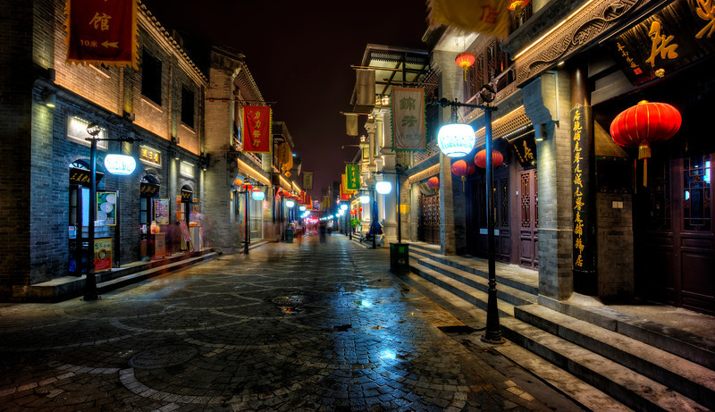 """<h2>Into the Night</h2>                     <br/>The restaurants all closed early in this area of Beijing, but the lights stayed on. So that was the perfect time to get some shots of the scene without a bunch of people in the frame mucking it up.<br/><br/>I can't tell you how many hours of my life I spend waiting for people to get out of the way. I mean, it's not a horrible thing… because at least I'm usually in visually interesting people while waiting on people!<br/><br/>- Trey Ratcliff<br/><br/><a href=""""http://www.stuckincustoms.com/2013/07/24/into-the-night/"""" rel=""""nofollow"""">Click here to read the rest of this post at the Stuck in Customs blog.</a>"""