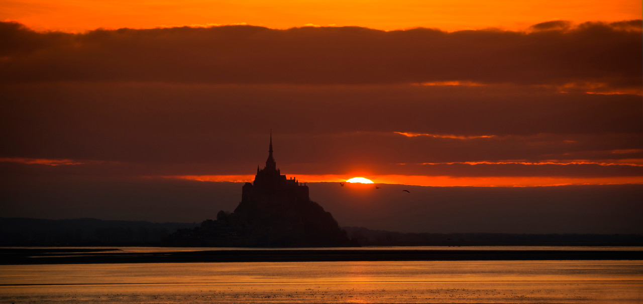 Mont Saint Michel at Sunset Oh my god getting to this location at the last second was difficult and lucky.I started the wild car ride about 30 minutes beforehand inside that walled city. I looked on Google Maps to figure out how to get to this exact spot. Now, I had no mobile internet, so I basically had to memorize the way here. It required going through, and I kid you not, about seven different roundabouts, each one exiting in a strange, non obviously spot. Anyway, to my and Tom's surprise, I exited each one perfectly and made it here with ZERO mistakes. Note that I am not nearly always this flawless, but it worked out and we got here just in time for sunset!- Trey RatcliffClick here to read the rest of this post at the Stuck in Customs blog.