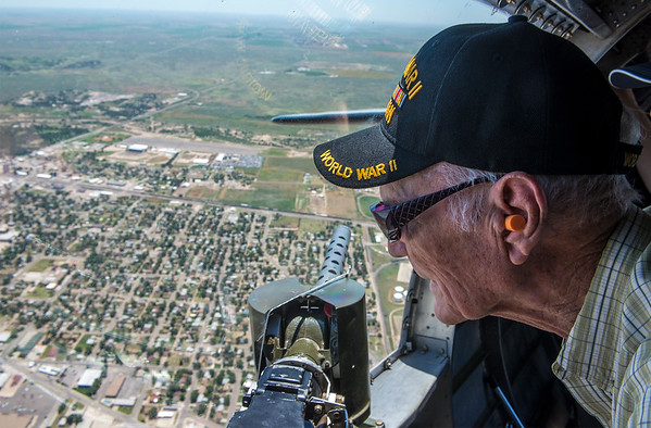 "World War II veteran of the Navy Burl Lovings peers out of a machine gunner's bay in a B-17G bomber as it flies over Garden City Monday. The plane, named ""The Sentimental Journey"" is a fully restored Army bomber from WWII that served in Europe."