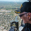 """World War II veteran of the Navy Burl Lovings peers out of a machine gunner's bay in a B-17G bomber as it flies over Garden City Monday. The plane, named """"The Sentimental Journey"""" is a fully restored Army bomber from WWII that served in Europe."""