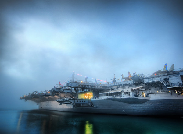 The Carrier I've been wanting to process this photo forever -- I love carriers.  This one is open to the public, but I arrived too late to get up on the deck...  So I was stuck on the ground level -- but then a sweet fog rolled in to cover part of the carrier.    - Trey Ratcliff  Read more here at the Stuck in Customs blog.