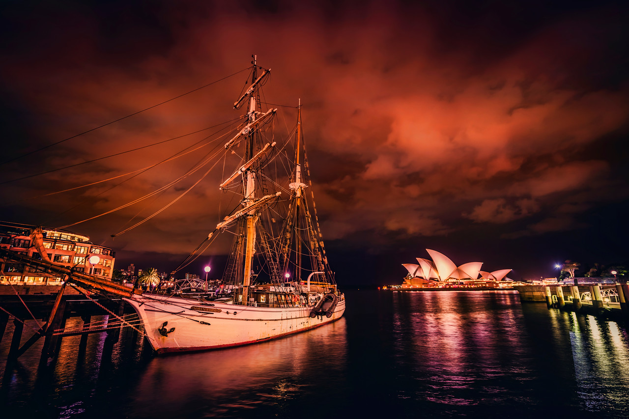 """Awesome Ship in Sydney Harbor Tom and I walked down to the Rocks one night, which is one of the oldest parts of the Sydney Harbor. I was wondering, actually, if I should spell it """"harbour"""" now that I live down thisaway. I do like the British spellings of things… they seem so much more… well, British and sophisticated. I guess I'll just stick with """"harbor"""" – I don't want people thinking I've turned native so quickly.Anyway, the ship was moving a lot in the sea, so I had my ISO up pretty high to compensate. Usually, what I'll do in this situation is take a normal set of brackets at a low ISO to get a nice HDR shot, and then I'll take another at high ISO to freeze the movement… and then I do my best to Frankenstein it all together.- Trey RatcliffClick here to read the rest of this post at the Stuck in Customs blog."""