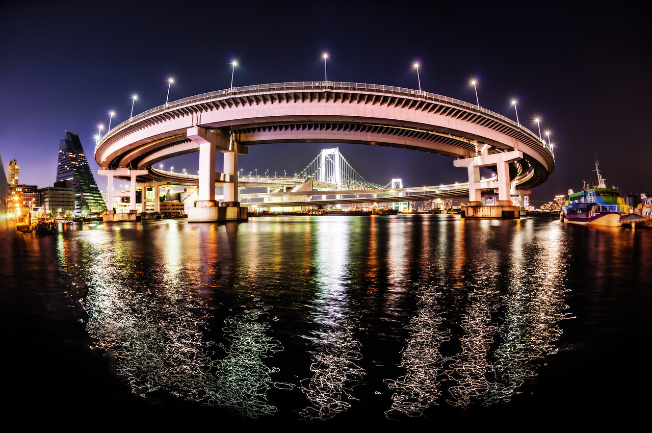 The Rainbow Bridge in Tokyo Thank you very much to Takahiro-san for taking us to this place!  He took Tom and I here one evening and helped us to find some really interesting angles of this awesome loopty-loop thing. The only way I was able to get the whole thing in was to use the fisheye — see my Nikon 16mm Fisheye review here.One thing that surprised me about this shot was the pattern the lights made on the water very close to me. It was like laser-light painting!- Trey RatcliffClick here to read the rest of this post at the Stuck in Customs blog.