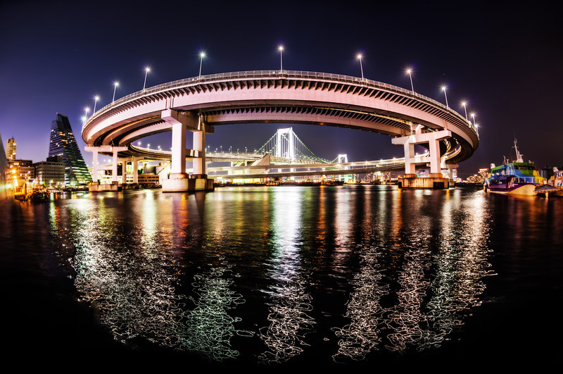 "<h2>The Rainbow Bridge in Tokyo</h2> <br/>Thank you very much to Takahiro-san for taking us to this place! <br/> <br/>He took Tom and I here one evening and helped us to find some really interesting angles of this awesome loopty-loop thing. The only way I was able to get the whole thing in was to use the fisheye — see my Nikon 16mm Fisheye review <a href=""http://www.stuckincustoms.com/nikon-fisheye-16mm-lens-review/"" rel=""nofollow"">here.</a><br/><br/>One thing that surprised me about this shot was the pattern the lights made on the water very close to me. It was like laser-light painting!<br/><br/>- Trey Ratcliff<br/><br/><a href=""http://www.stuckincustoms.com/2013/05/28/the-rainbow-bridge-in-tokyo/"" rel=""nofollow"">Click here to read the rest of this post at the Stuck in Customs blog.</a>"