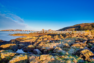 Looking Over to Portencross & Little Cumbrae From Seamill Bay on a Bright but Cold January Day with the Cold Morning Sun Reflecting on the Rocky Lichens Covered Shoreline