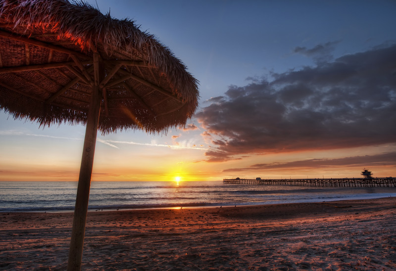 """<h2>Under the Umbrella at Sunset</h2> <br/>We took this during our fun PhotoWalk in San Clemente. It's a wonderful beach there - not too crowded, a perfect beach, and an idyllic pier.  Just throw in a few clouds, and we end up with a perfect sunset!<br/><br/>Every 100 feet or so, these thatched-roof umbrellas are spread out.  Composing with these and a wide-angle lens is kind of challenging, but fun.  I noticed that after I got a wide-angle lens that it opened up a whole new range of compositional complexities. Walking around a scene has to be done with a whole new perspective, since you are able to capture more than a human can see in a single viewing-cone.  But, the challenge is kind of fun to compensate for the lens and try to put together something that feels right.<br/><br/> - Trey Ratcliff <br/><br/>The rest of this entry can be found <a href=""""http://www.stuckincustoms.com/2010/10/24/under-the-umbrella-at-sunset"""">here</a> at the Stuck in Customs blog."""