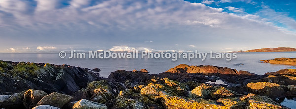 A Lichen Covered Rocky Shore Accross to Arran Covered in Winter Snows