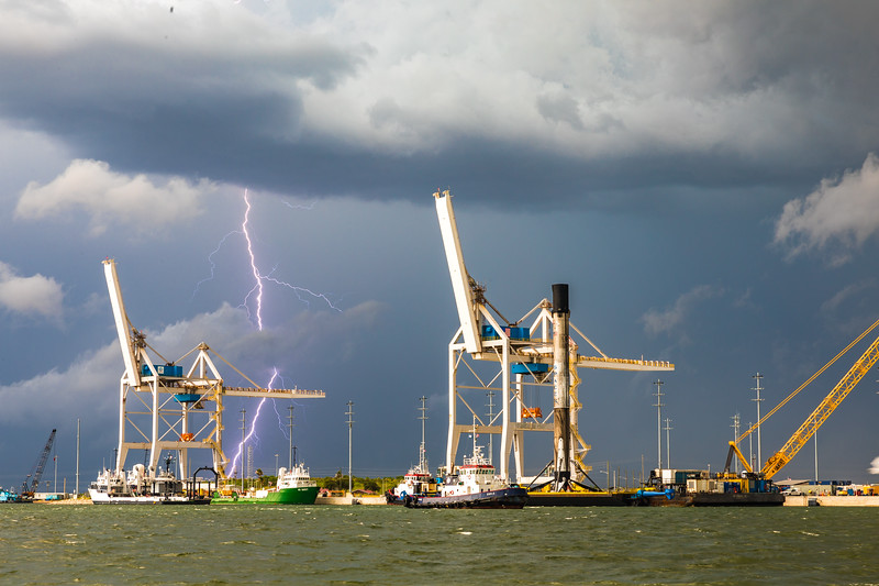The SpaceX Falcon 9 being returned to port just days after landing at sea as lightning strikes in the distance.