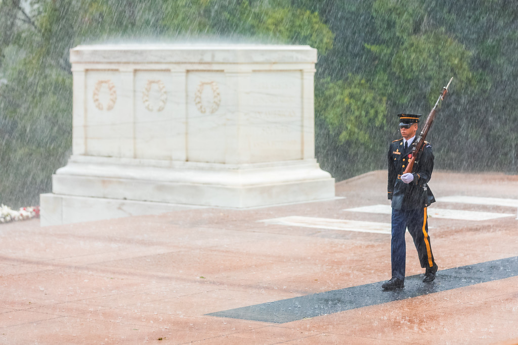 A US Army Tomb Guard Sentinel walks in the pouring rain guarding the Tomb of the Unknown Soldier in Arlington National Cemetary.