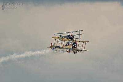 Painterly image of vintage milltary biplanes in a dogfight. Bremont Great War aerobatic display team.