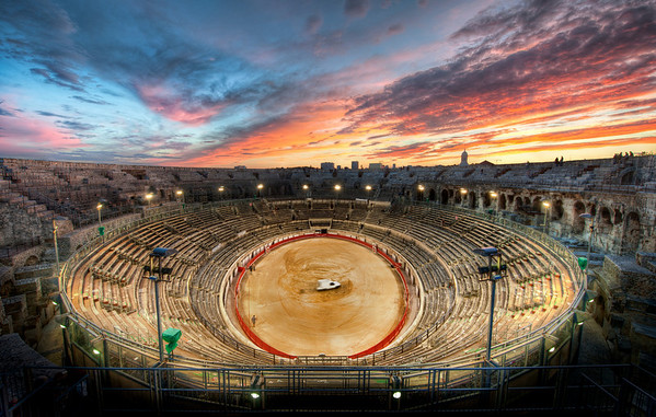 The Gladiator Arena at Sunset While visiting Fabien in Nimes, there was a bullfight going on inside this ancient Roman gladiator arena.  The further south you go in France, the more likely you are to find the old influence of the Spanish bullfights.  It's pretty violent, yes?  Yes.  In fact, if you zoom in, you can still see blood that has been smeared across the arena by the smearing-truck.Once the crowd started to clear out, a perfect sunset settled upon us.  It was just Fabien, my wife, and I, and it was a very nice night.  After the bullfight, we walked around to take a lot of photos of this amazing evening, Fabien took us to his favorite little secret French restaurant down one of the side streets.  Perfect!- Trey RatcliffClick here to read the rest of this post at the Stuck in Customs blog.
