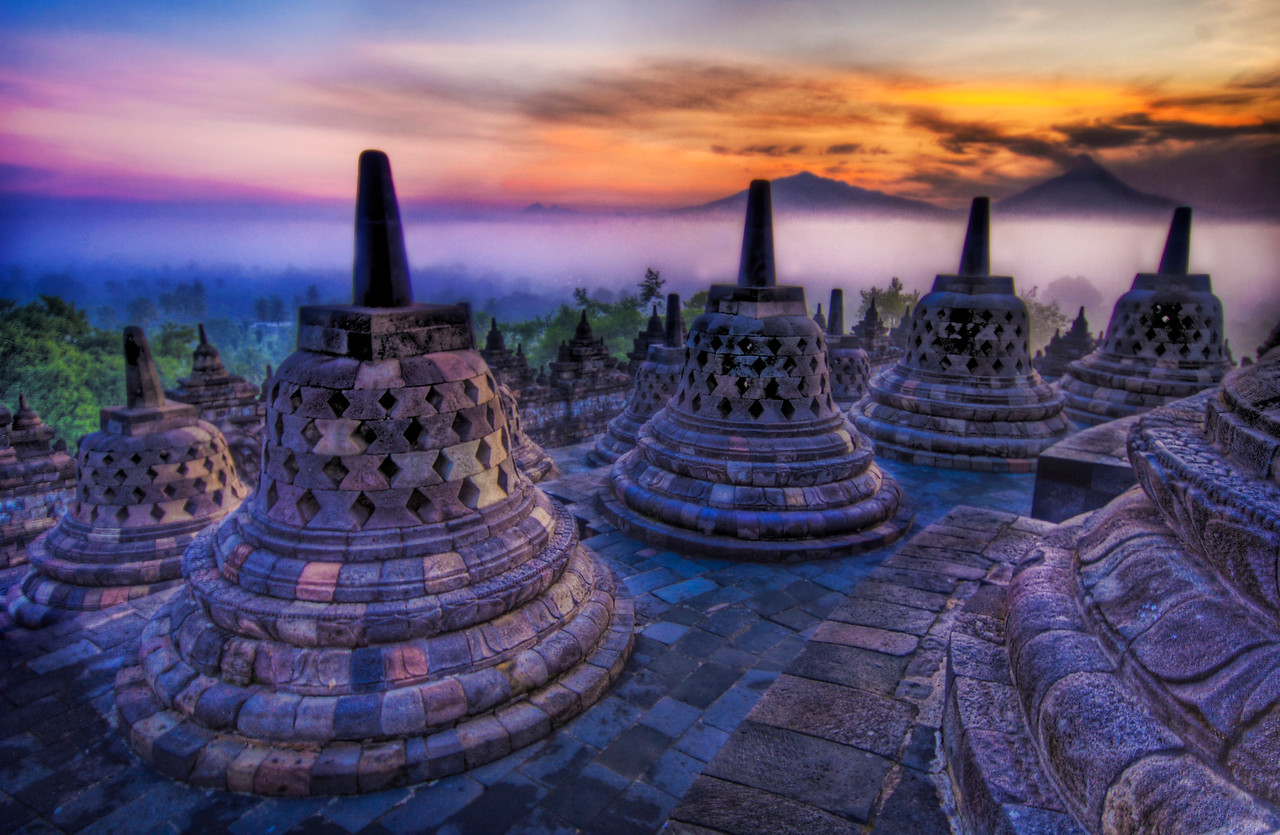 "The Caged Buddhas Look Outward Towards the Sunrise If you want to see how I made this (and how you can too!), visit my HDR Tutorial.  I hope it gives you some new tricks!Each of these ""bells"" is really a stone cage that houses a Buddha statue that is seated, facing outwards.  At this time in the morning, you can take little flashlights and peer inside the cages.  It's all very eerie and fun...In the distance, you can see a few volcanoes poking through the mist.- Trey RatcliffClick here to read the rest of this post at the Stuck in Customs blog."