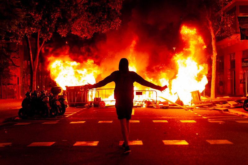 Epic powerful scene of young catalan protester walking against huge fire with arms wide  open in the background at night during riots with police expressing anger and power Barcelona, Spain - 16 october 2019