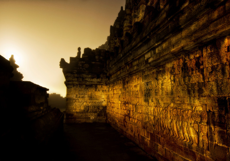 The Dark Temple Corridor in Morning Mist at 4 AM I arrived at the temple of Borobudur a little after 4 AM. I had a tiny disposable flashlight, and, other than my driver idling about a mile away, I was the only person here. In fact, it was my second day in a row to do this, since I had so much fun the first. I was there with my friend Will, and he decided to sleep in the second day… but I had a few shots in mind I wanted to grab before the sun came up. There were these strange argon lights around the temple to light up areas of excavation. They cast a gloomy and surreal light on the Buddhist reliefs that make concentric circles up to the top. I was able to get about 45 minutes of nice darkness with unexpected light until the sun started to appear over the nearby volcanoes and jungle mist. - Trey RatcliffClick here to read the rest of this post at the Stuck in Customs blog.